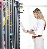 Young female engineer businesswoman with modern laptop in network server room