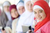 stock photo of muslimah  - Muslim and Arabic girls standing together in line row - JPG