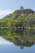 picture of winona  - A limestone rock formation on top of a hill with a reflection in a lake - JPG