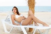 foto of leggy  - Pretty leggy woman in white swimsuit lying on the beach bed - JPG