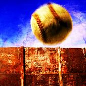 Baseball in air flying over rusted wall with blue sky