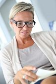 stock photo of stressless  - Mature blond woman reading book  - JPG