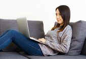 Woman on sofa using laptop