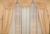 image of tassels  - classic beige curtain hanging on a window  - JPG