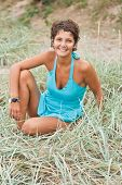 picture of brunete  - portrait of attractive brunet woman in blue sitting in a grass - JPG