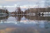 stock photo of mudslide  - large puddle reflects spring blue sky and clouds on crossroads of city - JPG