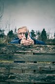 picture of barricade  - Senior man aiming a gun at you and hiding behind barricade outdoors - JPG