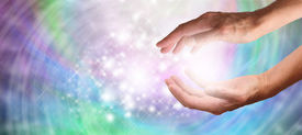 picture of senses  - Close up of healing hands outstretched with beautiful sparkling swirling energy on wide banner - JPG