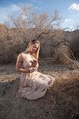 picture of bhakti  - Young woman in a beautiful dress kneeling in a secluded desert landscape - JPG