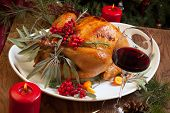 pic of turkey dinner  - Roasted turkey garnished with sage rosemary and red berries in a tray prepared for Christmas dinner - JPG