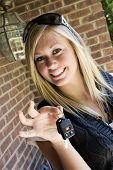pic of car key  - Teenage girl holding out the keys to her car - JPG