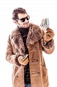 foto of hustler  - a young man wearing a sheepskin coat isolated over a white background holding Euro banknotes - JPG