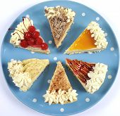 stock photo of pumpkin pie  - Thanksgiving apple pecan cherry caramel pumpkin spice and chocolate cream cheesecake pie on blue polka dot platter against a white table - JPG
