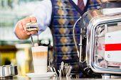 picture of mug shot  - Barista in cafe or coffee bar preparing pouring espresso shot in glass of latte macchiato - JPG