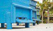 stock photo of bee-hive  - Row of blue bee hives with bees - JPG