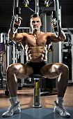 image of execution  - very brawny guy bodybuilder execute exercise on gym apparatus Butterfly Machine in gym - JPG