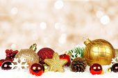stock photo of twinkle  - Gold and red Christmas ornament border in snow with twinkling gold light background - JPG