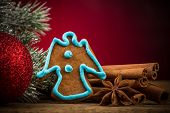 image of desert christmas  - Christmas gingerbread cookie red ball and anise on wooden table with red background - JPG
