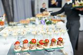 image of catering  - Waiter with meat dish serving catering table with food snacks - JPG