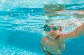 foto of crystal clear  - Small boy swimming wearing goggles under the crystal - JPG