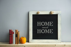 stock photo of chalkboard  - chalkboard frame on the grey wall with books and pumpkin HOME SWEET HOME - JPG