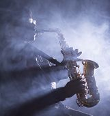 image of saxophone player  - African American jazz musician playing the saxophone through smokey light in club