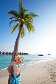 Постер, плакат: Молодая красивая девушка стоит рядом с Пальма на фоне океана Мальдивы