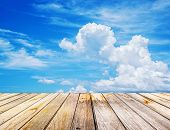 pic of floor covering  - Perspective View to sparse white clouds in the blue sky and background of wood floor texture - JPG