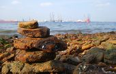 stock photo of shipyard  - Rocks on the coast of the sea with shipyard as background - JPG