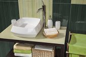 image of bathroom sink  - detail of a modern bathroom with sink and accessories bathroom cabinet and green bathroom tiles - JPG