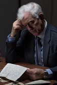 stock photo of lonely  - Lonely aged man reading old letter from a lover - JPG