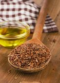 pic of flax seed oil  - Brown flax seeds on spoon and flaxseed oil on wooden table - JPG