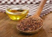 foto of flax seed oil  - Brown flax seeds on a spoon and flaxseed oil on wooden table - JPG