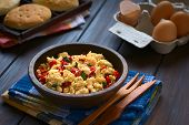 image of scrambled eggs  - Scrambled eggs made with red bell pepper and green onion in rustic bowl with toasted bread and eggs in the back photographed with natural light  - JPG