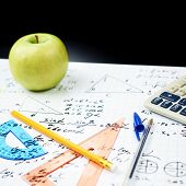 stock photo of math  - Studying math back to school composition of the green apple and some stationery office supplies lying over the sheet filled with trigonometry equations and formulas - JPG