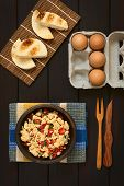 image of scrambled eggs  - Overhead shot of scrambled eggs made with red bell pepper and green onion in rustic bowl with toasted bread and eggs photographed on dark wood with natural light - JPG