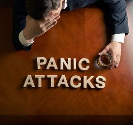 pic of panic  - Phrase Panic Attacks made of wooden block letters and devastated middle aged caucasian man in a black suit sitting at the table with the glass of whiskey - JPG