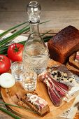 foto of vodka  - Vodka and smoked meat on wooden table - JPG