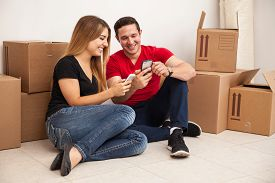picture of social housing  - Cute young couple moving to a new house and social networking with their smartphones - JPG