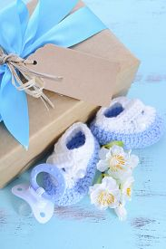 stock photo of teething baby  - Baby shower Its a Boy natural wrap gift with gift box baby booties and dummy on pale blue shabby chic rustic wood table - JPG