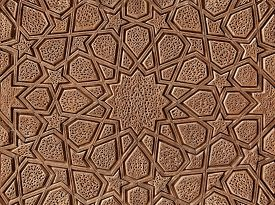 image of motif  - Islamic flowers and stars motif pattern carved on the surface of an old wooden door - JPG