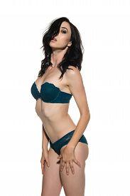 stock photo of slender  - Pretty young slender brunette in teal lingerie - JPG