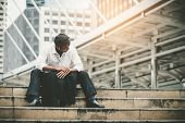 Tired Or Stressed Businessman Sitting On The Walkway In The City After His Work. Image Of Stressed B poster