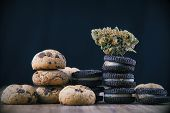Detail of single cannabis nug over infused chocolate chips cookies - medical marijuana edibles conce poster
