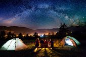 Friends Hikers Sitting Beside Camp And Tents In The Night poster