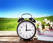 Alarm clock with books and spring blooming branch on wooden table against landscape background. Time poster