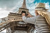 Woman tourist selfie near the Eiffel Tower in Paris under sunlight and blue sky. Famous popular tour poster