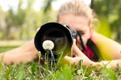 photographer - girl making pictures of flower in nature