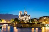 Notre Dame De Paris With Cruise Ship On Seine River At Night In Paris, France poster