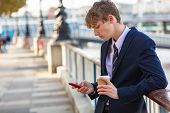 Male young adult teenager wearing suit and tie using smart cell phone for socail media and drinking  poster